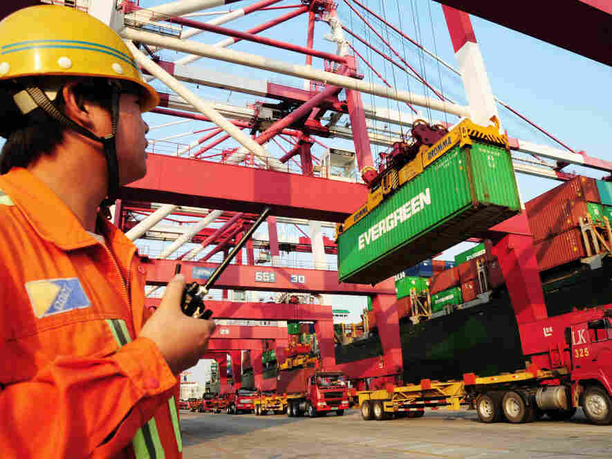 A worker monitors the loading of containers on to a ship at a harbor in China's Shandong province. Under a new U.S. law, Chinese food exporters will now have to share more food safety information with American food importers.