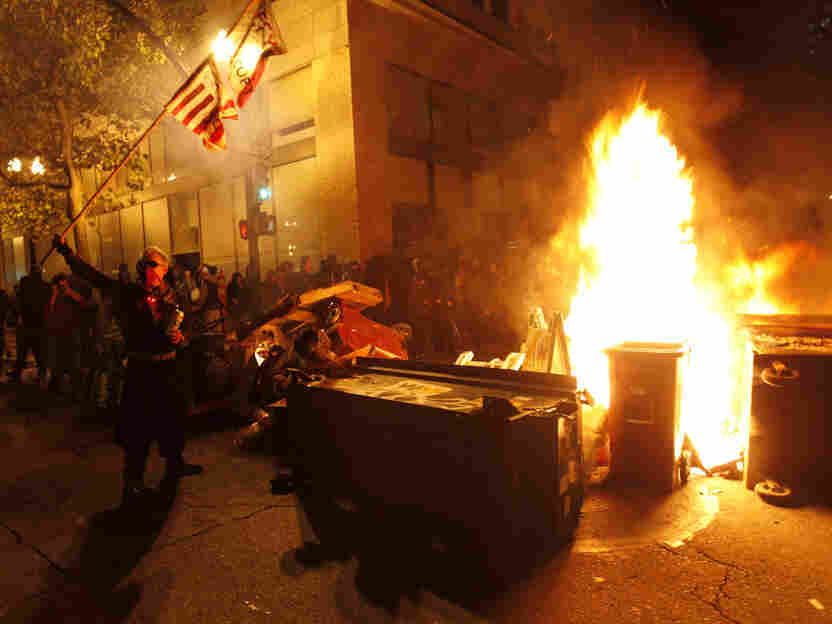 Occupy Oakland protesters set trash on fire to make a barricade as police officers form a line to disperse them on Nov. 3., in Oakland, Calif.