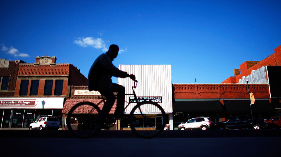 A biker rides through downtown Ponca City, Okla. After 726 complaints and close to $20 million in settled lawsuits against Continental Carbon, there are very few reports of black dust tainting the town. (NPR)