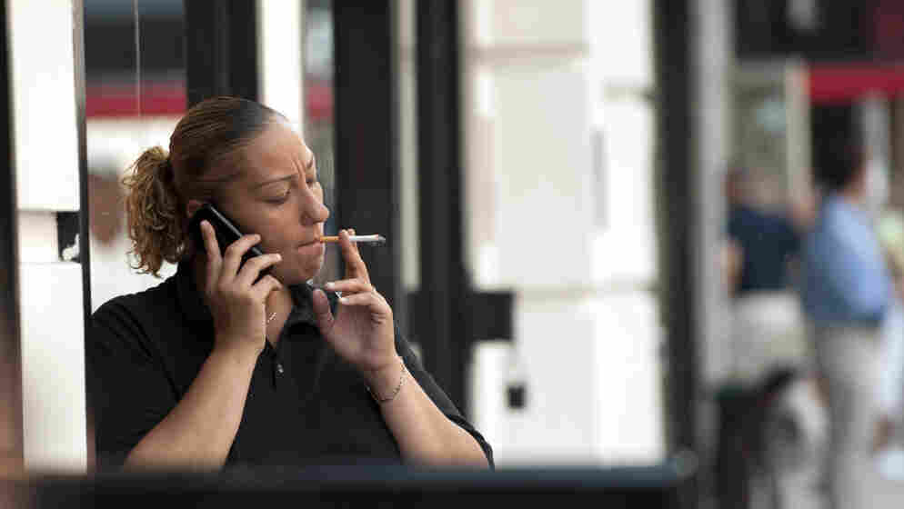 A woman smokes outside an office building in New York City.