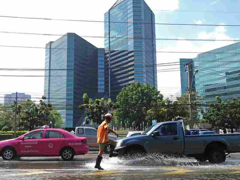 A traffic policeman directs vehicles during flooding in Bangkok on Nov. 3. Parts of Bangkok are being actively protected by floodgates, and water levels there are low.