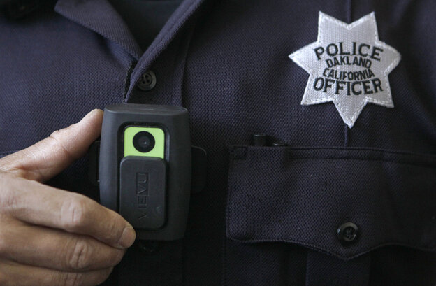 Officer Huy Nguyen shows a video camera worn by some officers in Oakland, Calif. Oakland and dozens of other police depa
