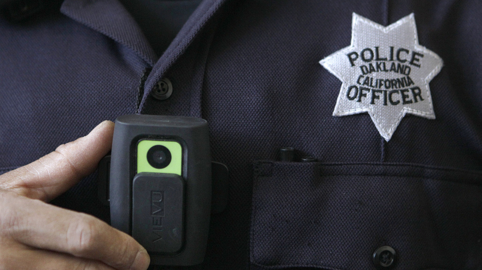 Officer Huy Nguyen shows a video camera worn by some officers in Oakland, Calif. Oakland and dozens of other police departments across the country are equipping officers with tiny body cameras to record anything from a traffic stop to a violent crime in progress.  (AP)