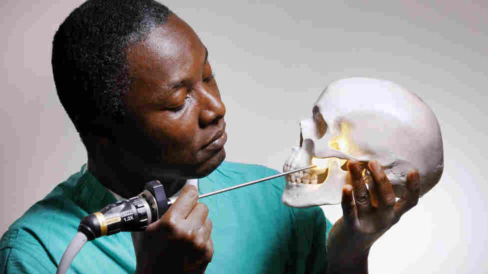 Striking a pose like Hamlet, Kofi Boahene, a surgeon at Johns Hopkins Hospital, peers through the natural opening under the cheekbone and above the jaw that he uses for surgery.