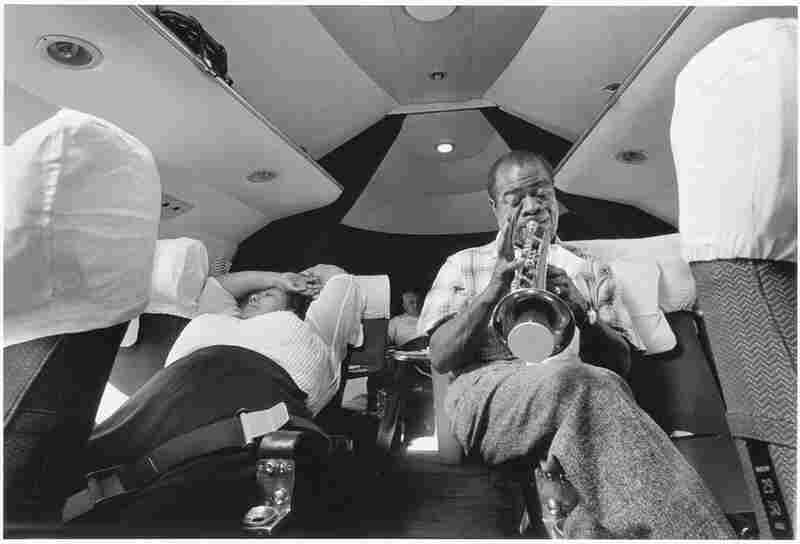 Louis Armstrong practices during a plane ride from Nigeria to the Gold Coast in 1956.