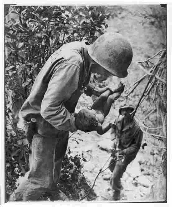 Famed photographer W. Eugene Smith captures a tender moment between an American soldier and a wounded infant in Saipan during World War II in 1944.