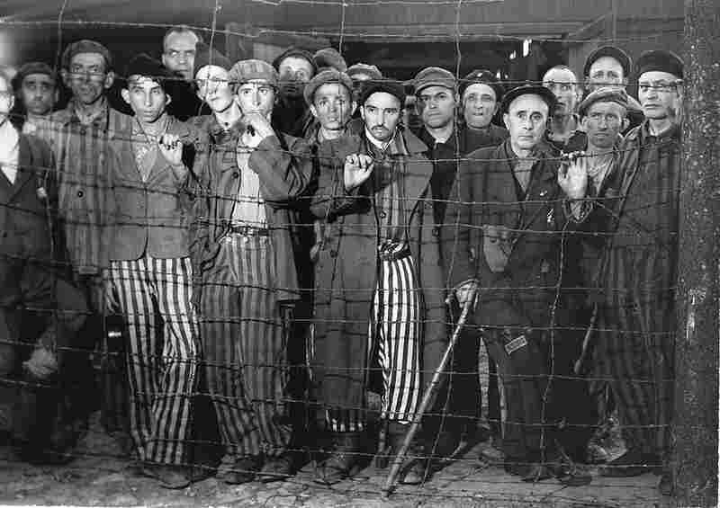 Hollow-eyed prisoners at Buchenwald concentration camp stare through a barbed wire fence after their liberation by advancing American forces in April 1945.