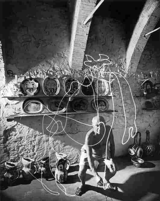Artist Pablo Picasso uses a flashlight to draw a centaur in the air at Madoura Pottery in France in 1949.