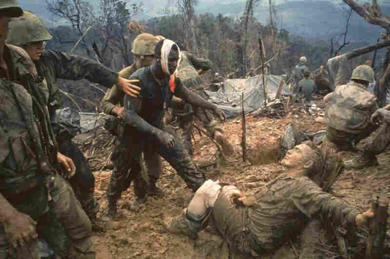 Wounded Marine Gunnery Sgt. Jeremiah Purdie (center) is led past stricken comrades after a fierce firefight during the Vietnam War.