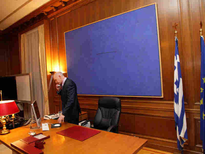 Greek Prime Minister George Papandreou makes a phone call on Sunday after his meeting with Greek President Carolos Papoulias and opposition leader Antonis Samaras.