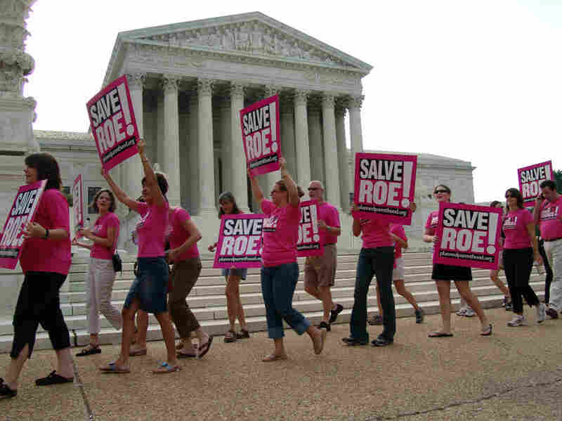 People supporting a woman's right to an abortion march in front of the U.S. Supreme Court in Washington, July 20, 2005, the day after John Roberts was nominated to become the court's chief justice.