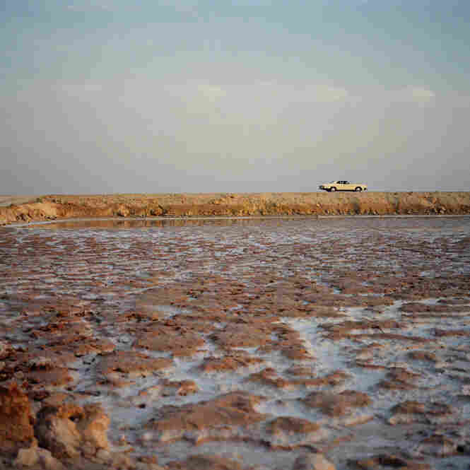 A car drives at the edge of a salt lake at Siwa Oasis, Egypt.