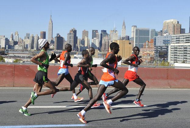 The men's leaders in the New York City Marathon cross the Pulaski Bridge running toward the borough of Queens on Sunday. The winner, Geoffrey Mutai, of Kenya, is at center rear, in green.