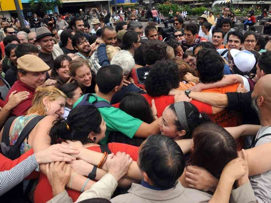 Hundreds of protesters embrace at the Culture square in San Jose, Costa Rica, on Oct. 15, 2011, during a worldwide demonstration against corporate greed and government cutbacks inspired by US 'Occupy Wall Street.'