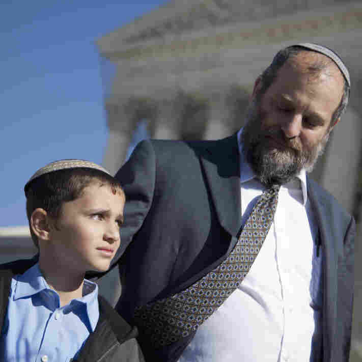 Ari Zivotofsky stands with his 9-year-old son, Menachem, outside the Supreme Court on Monday. Menachem was born in Jerusalem, and he and his parents want his U.S. passport to list his place of birth as Israel.