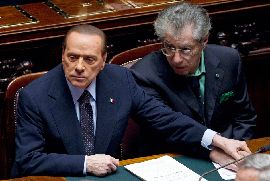Italian Premier Silvio Berlusconi, left, holds the hand of Reforms Minister Umberto Bossi during a must-watched vote at the Lower Chamber, in Rome, Tuesday, Nov. 8, 2011. (Andrew Medichini/AP)