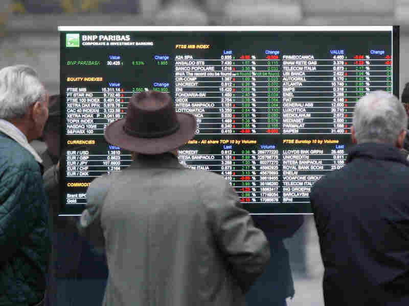 Men look at a stock exchange board monitor outside a bank in Milan last week. The country's economic problems have been mounting steadily.