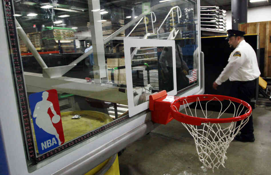 A security guard walks by a folded up NBA basket stored in the lower level of the TD Garden, the home of the Boston Celtics.