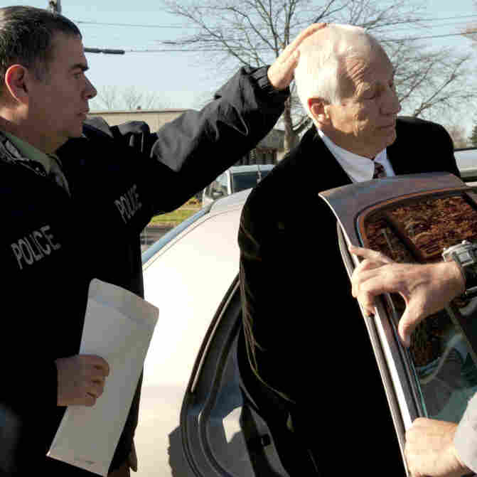 "In a photo provided by the Pennsylvania Office of Attorney General, former Penn State football defensive coordinator Gerald ""Jerry"" Sandusky, center, is placed in a police car iin Bellefonte, Pa., to be taken to the office of a Centre County Magisterial District judge on Saturday, Nov. 5, 2011."