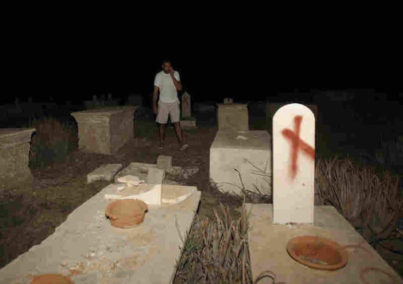 """A man stands near tombstones vandalized in a cemetery in Jaffa, Israel, on Oct. 8. Headstones at the Muslim and Christian cemetery were defaced with messages like """"Death to Arabs."""""""