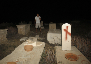 "A man stands near tombstones vandalized in a cemetery in Jaffa, Israel, on Oct. 8. Headstones at the Muslim and Christian cemetery were defaced with messages like ""Death to Arabs."""