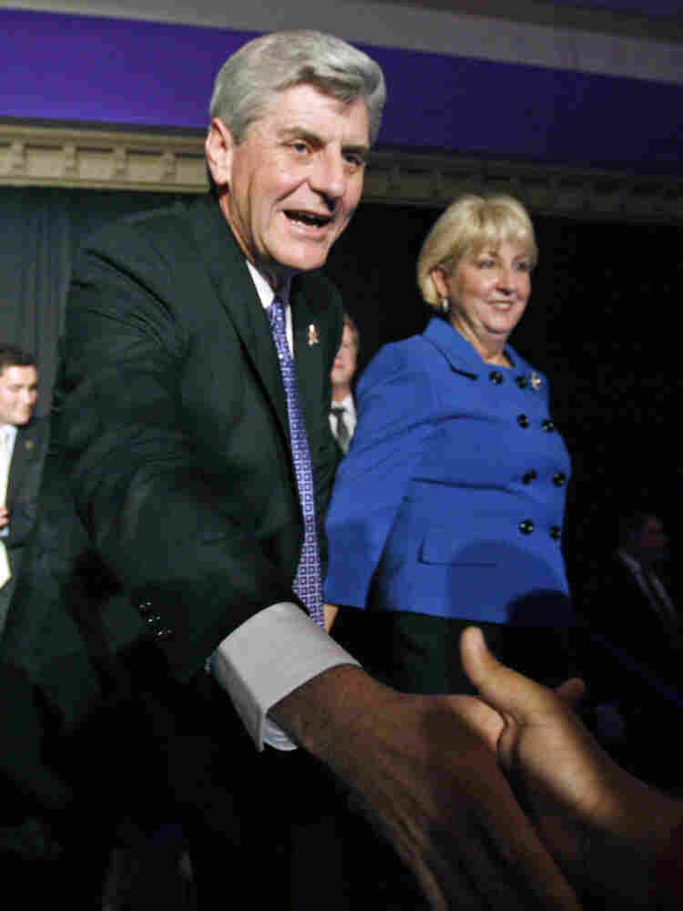 """Wife Deborah Bryant waits as Mississippi Governor-elect Phil Bryant thanks a supporter Tuesday at a victory party. Bryant supported a controversial amendment to the state's constitution on """"personhood."""""""