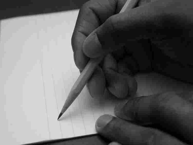 A hand taking a pencil to paper.