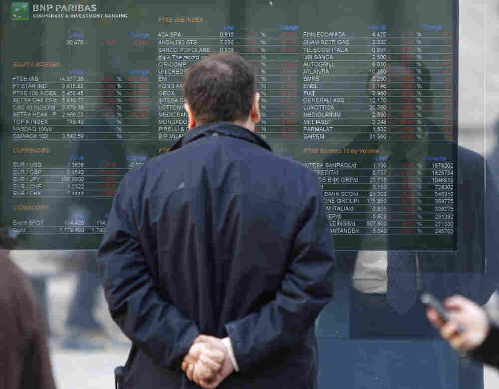 A man checks a stock exchange monitor outside a bank in Milan, Italy. Italy's key borrowing rate spiked Wednesday well above the 7 percent level that eventually forced other eurozone countries to seek b