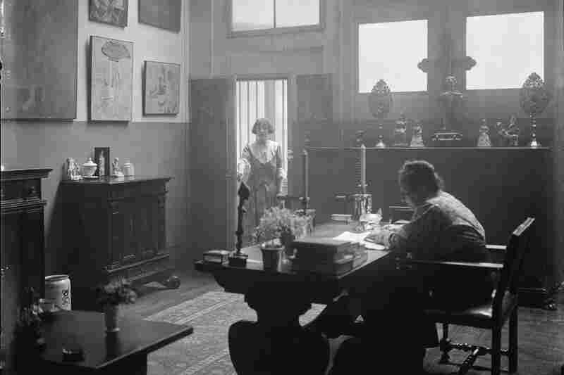 Stein said the artwork in her apartment influenced and inspired her writing — especially her cubist poetry. This 1922 photograph taken by Man Ray shows Stein seated at a desk and Toklas standing in the doorway of the small apartment.