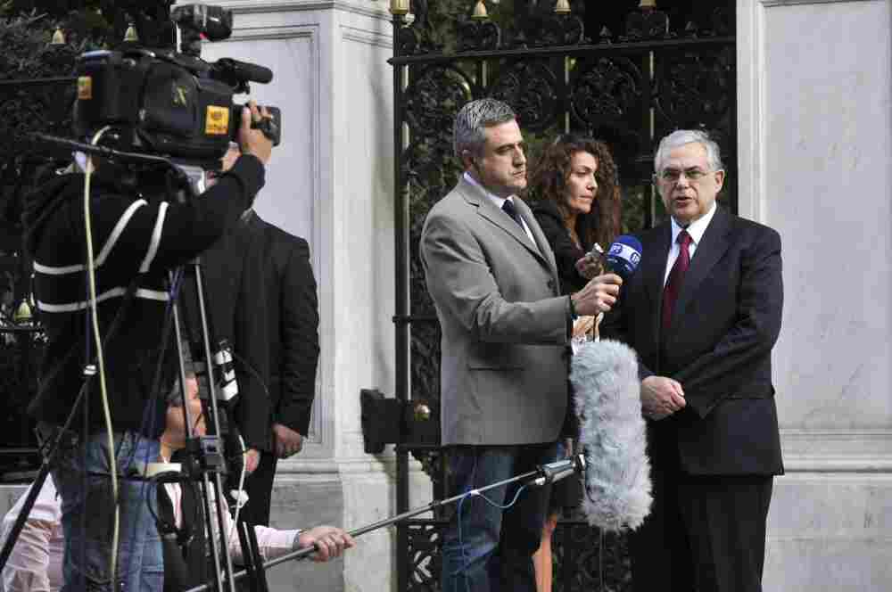 Greece's new prime minister-in-waiting Lucas Papademos (R) makes a statement to the national television (EPT) outside the Presidential Palace in Athens.