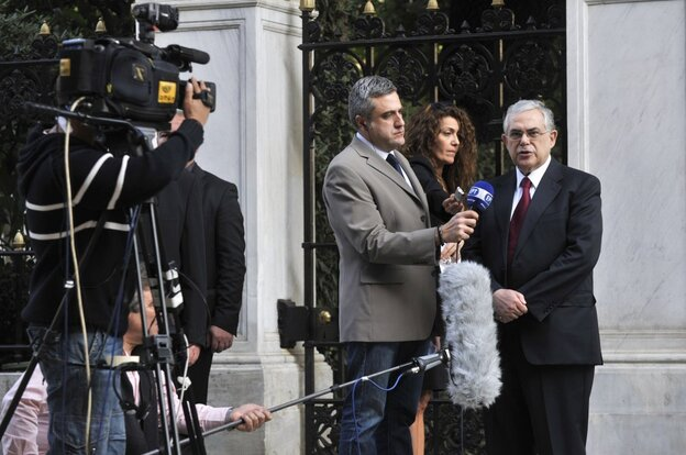 Greece's new prime minister-in-waiting Lucas Papademos (R) makes a statement to the national televi