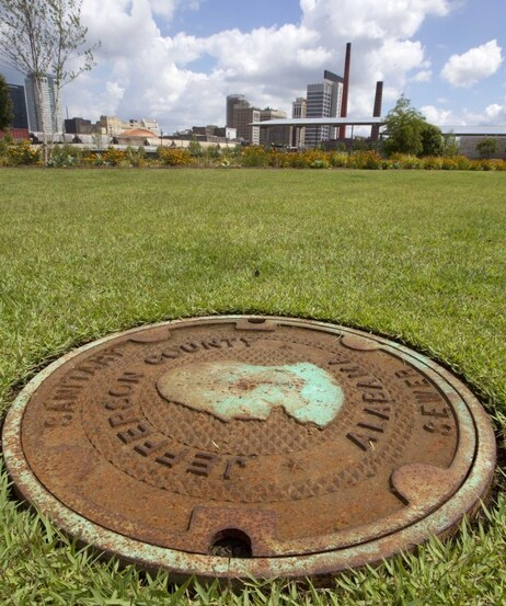This file photo shows a Jefferson County sewer manhole cover in Railroad Park in Birmingham, Ala. Leaders of Alabama's most populous county voted to file an estimated $4.1 billion bankruptcy.