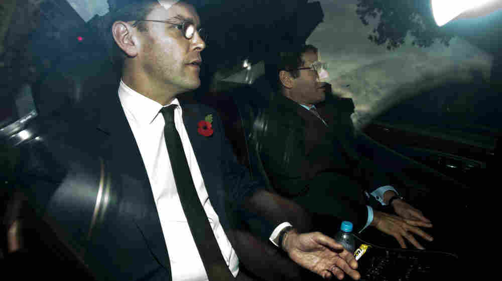 News Corp. executive James Murdoch, left, is driven away from a drive-in entrance at Portcullis House after his second appearance before British parliamentarians investigating the country's phone hacking scandal.