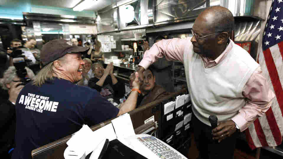 Republican presidential candidate Herman Cain shakes hands with Jeff Balaka, of Chelsea, Mich., while speaking at the Big Sky Diner in Ypsilanti, Mich., on Thursday. Despite allegations of sexual harassment that surfaced recently, Cain still enjoys the support of his conservative base.