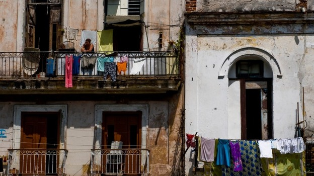 For the first time in 50 years, Cubans can now buy and sell homes. Here, a Cuban woman stands on the balcony of a dilapidated building earlier this month in Havana.