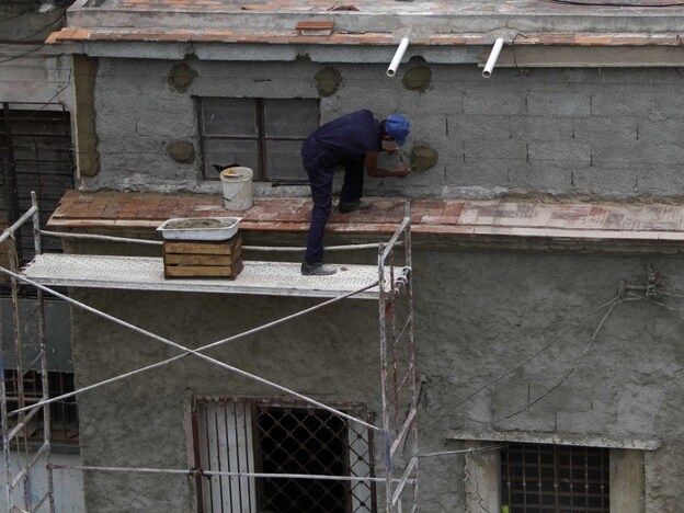 Antonio Gonzalez repairs the facade of a house in Havana in May. The new law means many property owners are now updating long-neglected buildings. Well-kept single family homes in prime neighborhoods are listed at $100,000 or more.