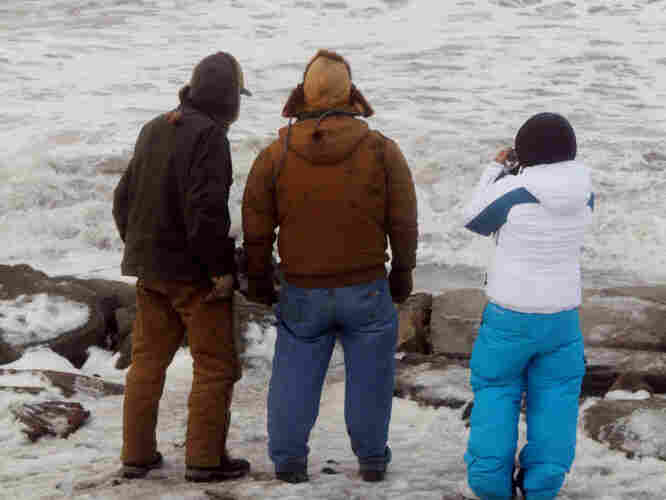 A trio get a closer look at the large waves cresting over the seawall just south of Nome's Front Street in Nome, Alaska, Wednesday., Nov. 9, 2011.