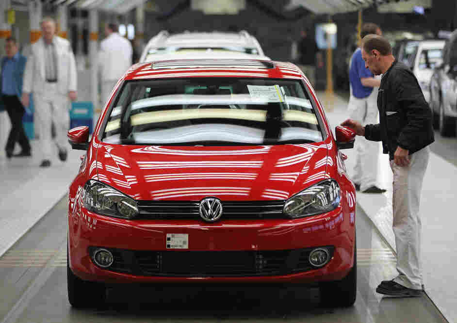 Workers prepare new Volkswagen Golf cars at a factory in Wolfsburg, Germany.