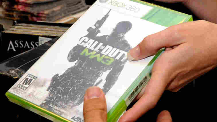 """A customer buys a copy of """"Call of Duty: Modern Warfare 3"""" for the Xbox 360 during a launch event for the highly anticipated video game."""