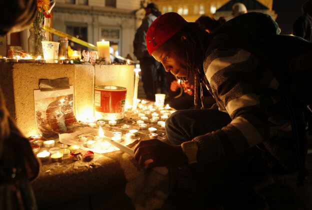 An Occupy Oakland demonstrator lights a candle after a m