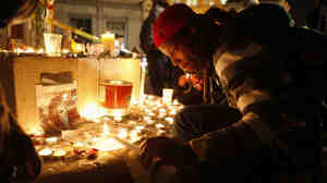 An Occupy Oakland demonstrator lights a candle after a man was shot and killed near the Occupy Oakland camp.