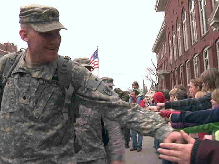 Cole Smith, who served as a driver and gunner in convoys looking for roadside bombs in Afghanistan, greets crowds in his hometown of Hancock, Mich.