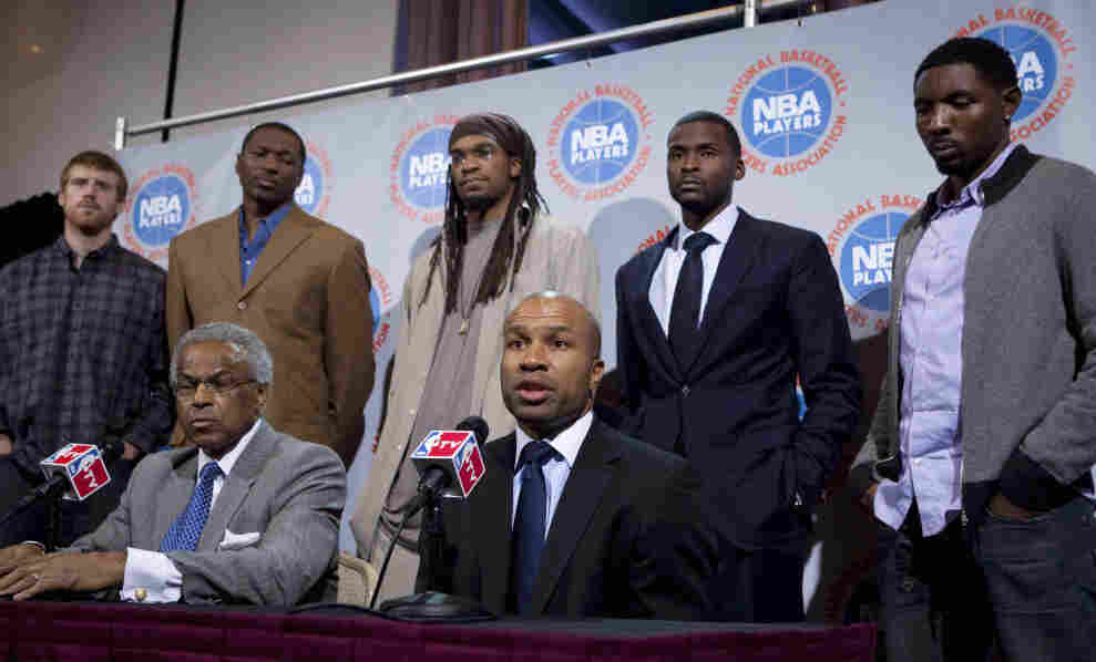 NBA Players Association president Derek Fisher speaks alongside executive director Billy Hunter. Matt Bonner, Theo Ratliff, Etan Thomas, Keyon Dooling and Roger Mason stand behind them.