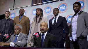 NBA Players Association president Derek Fisher speaks alongside executive director Billy Hunter. Matt Bonner, Theo Ratliff, Etan Thomas, Keyon Dooling and Roger Mason stand behind them.