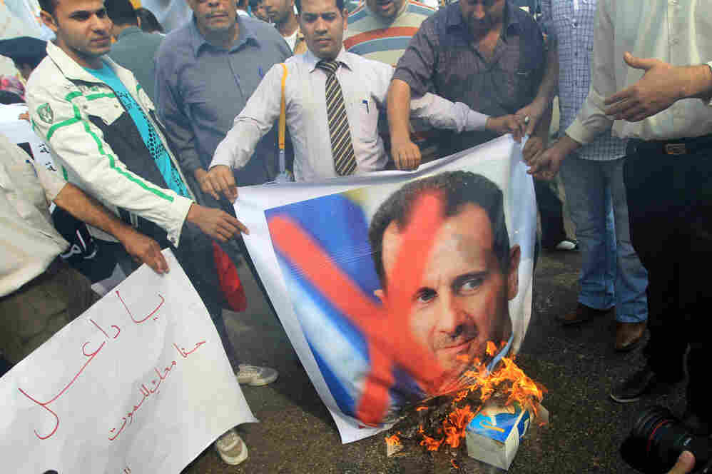 Protesters burn portraits of Syrian President Bashar Assad during a demonstration outside the Arab League headquarters in Cairo.