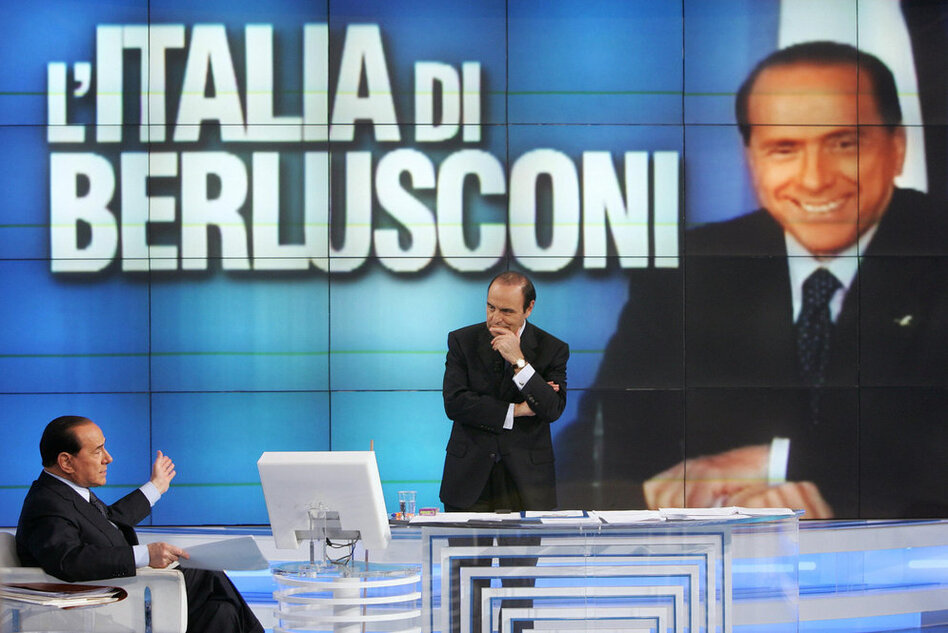 "Berlusconi (left) answers journalist Bruno Vespa's questions during a broadcast of ""Porta a Porta,"" an Italian TV talk show in 2006.  (Getty Images)"