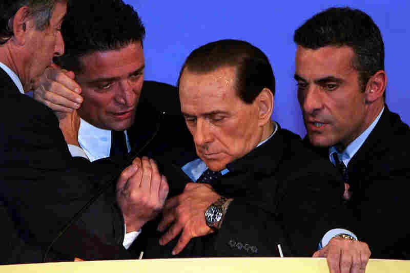 Silvio Berlusconi is supported at the podium by his personal doctor Umberto Scapagnini, left, and by two unidentified men, as he slumped during an emotional speech to political supporters in Montecatini Terme, Italy in 2006.