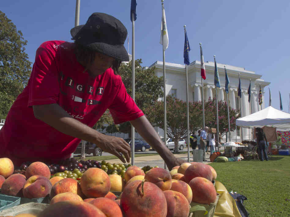 Desmond Brown sells fruits and vegetables at a farmer's market outside the Alabama Capitol in Montgomery, Ala.