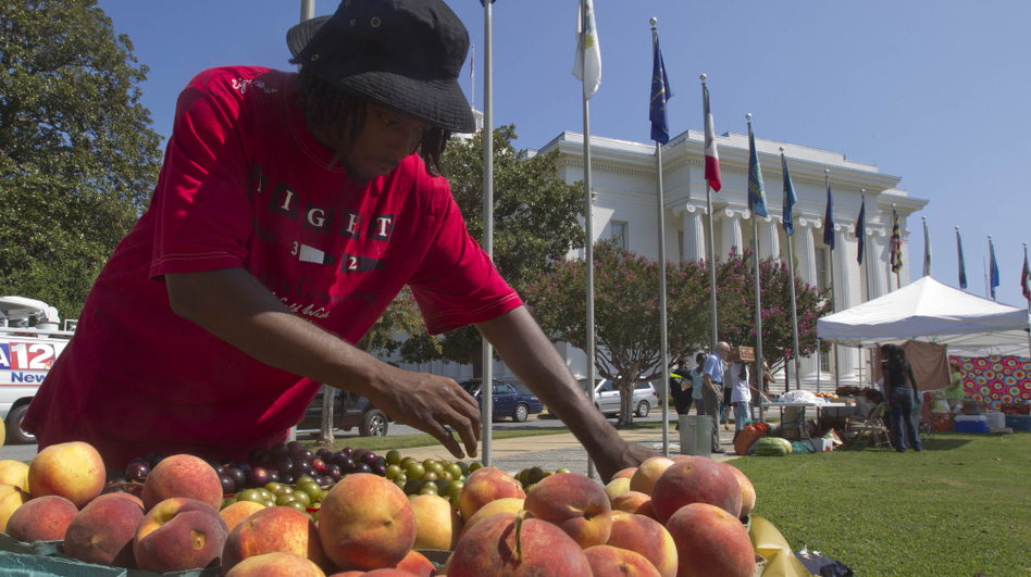 Desmond Brown sells fruits and vegetables at a farmer's market outside the Alabama Capitol in Montgomery, Ala. (AP)