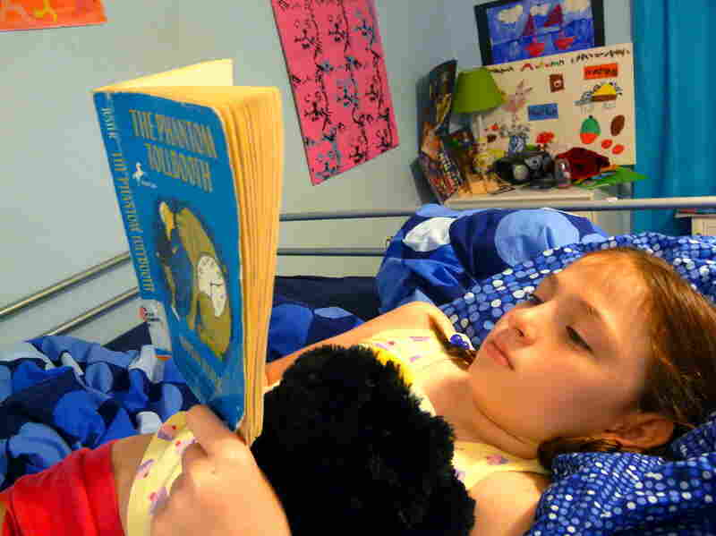 Rory Pennington, 8, relaxes with The Phantom Tollbooth at home in Jacksonville, Fla.